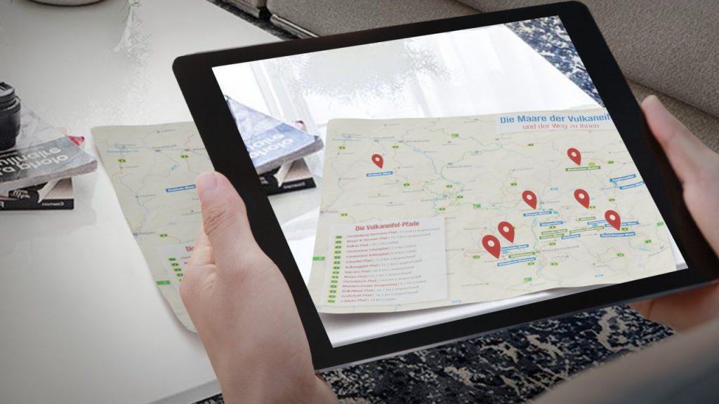 interaktive AR-Karte auf Tablet, welches Nutzer über reale Karte hält