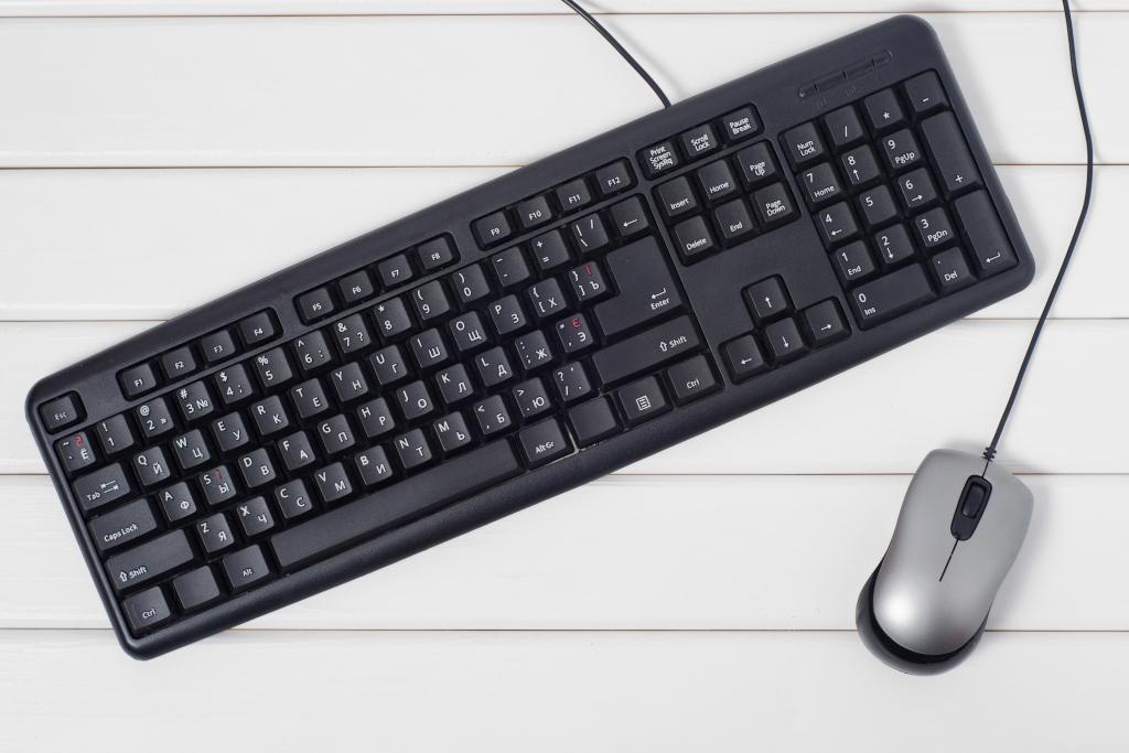Tastatur und Maus mit Kabel liegen auf weißem Holztisch