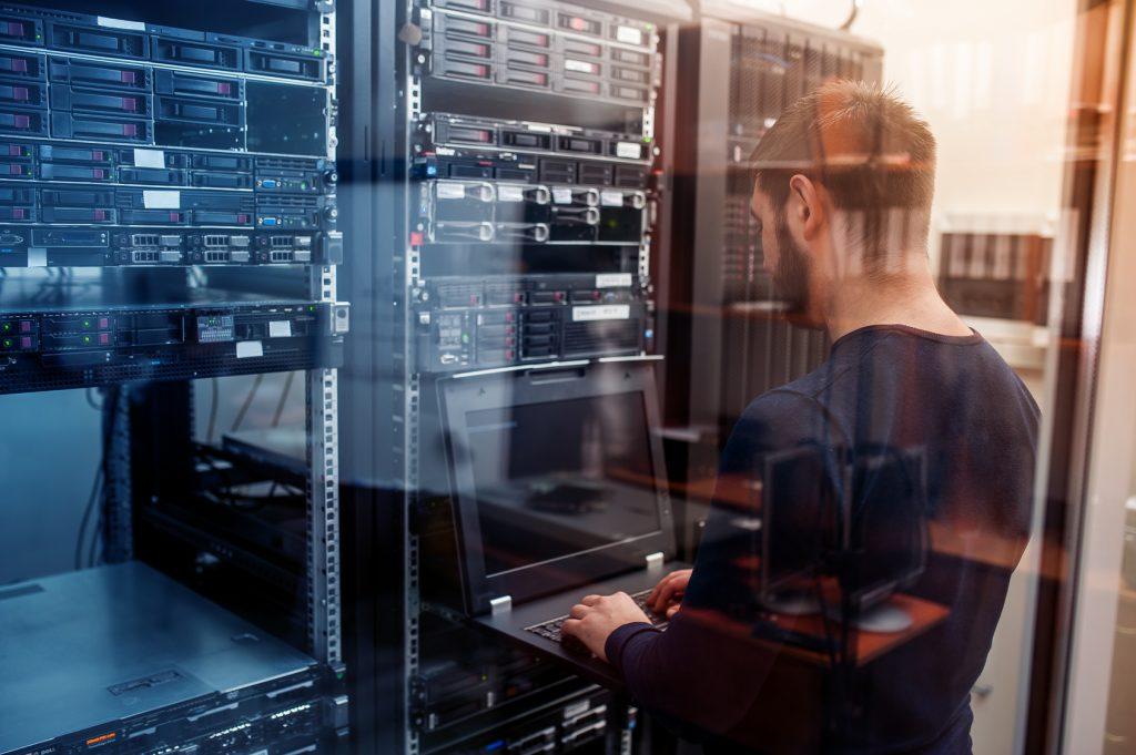 Mitarbeiter steht vor Serverschrank und arbeitet am Laptop