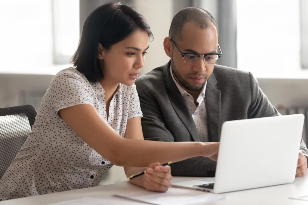 Junge Faru zeigt IT-Berater mit Brille und Anzug etwas auf dem Laptop