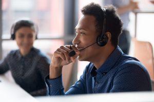 IT-Dienstleister Büro: junger IT-Service-Mitarbeiter lacht und spricht am Telefon mit IT-Kunden